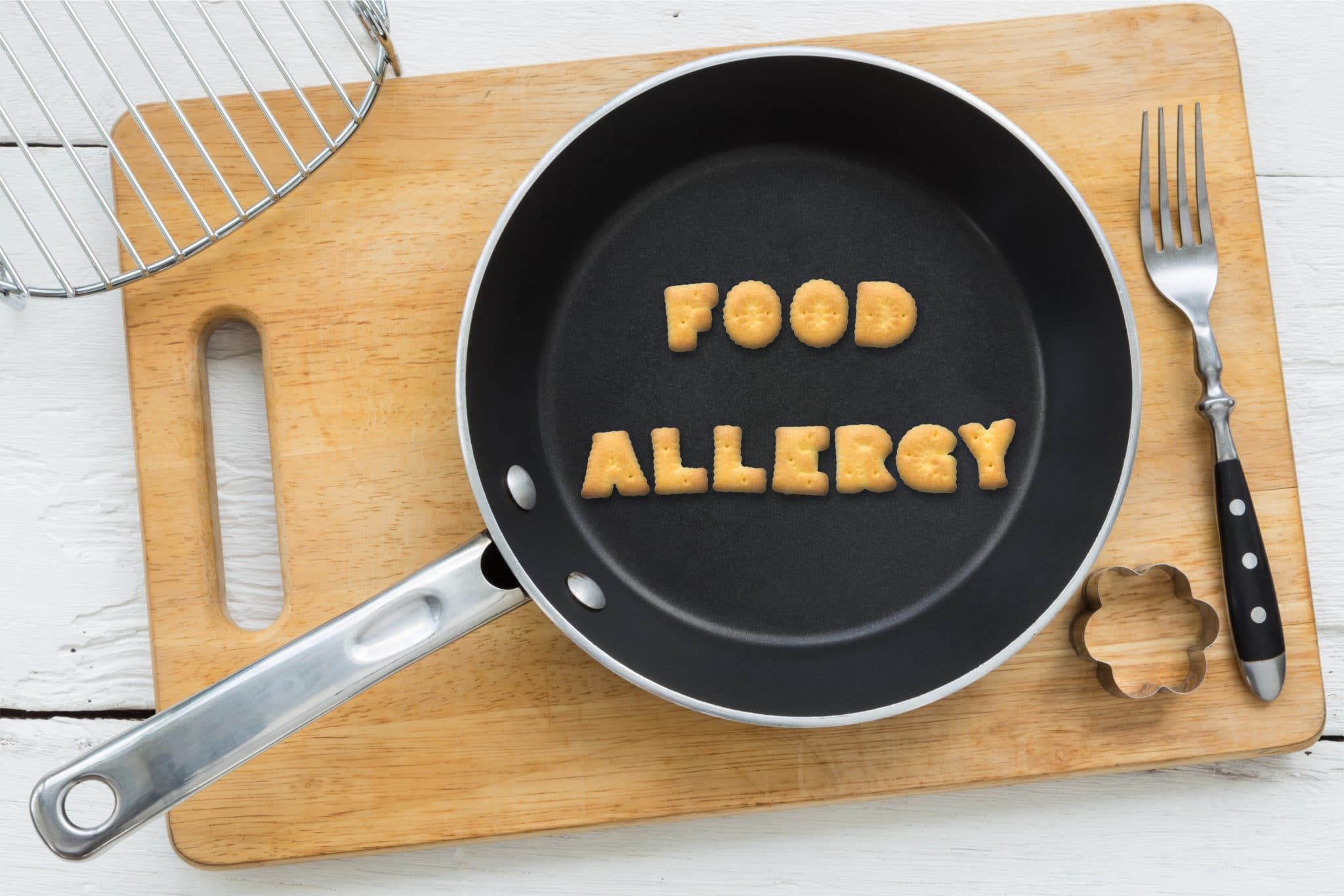 A pan with food representing letters that spell out the words food allergy